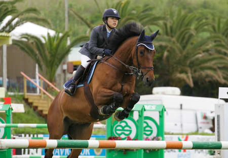 VIMEIRO, PORTUGAL - JUNE 5: Equestrian International Show Jumping 3* - Reiko Takeda (JPN) June 5, 2010 in Vimeiro, Portugal Stock Photo - 7124283