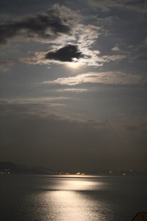 Full Moon Behind Clouds Reflecting On Garda Lake photo
