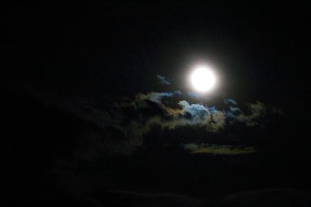 Full moon lightening clouds at black night sky photo