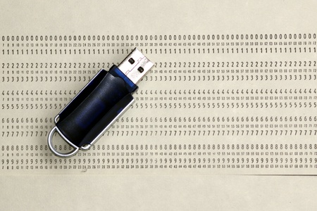 A blue USB Pen Drive over a blank punch card photo
