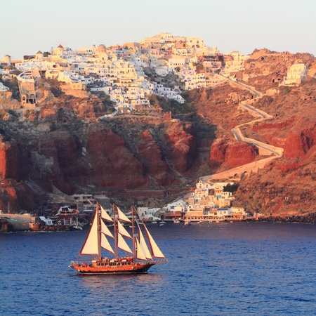 View Of Oia And Athinios Harbor With Gulet At Sunset - Santoriniland photo