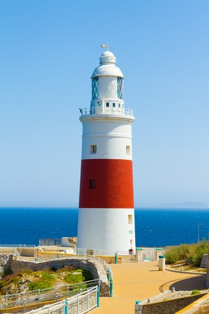 white and red lighthouse on the coast photo