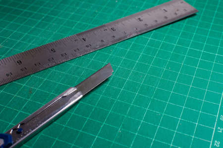 office stapler: Cutter and steel ruler on cutting pad, Office stationery tools.