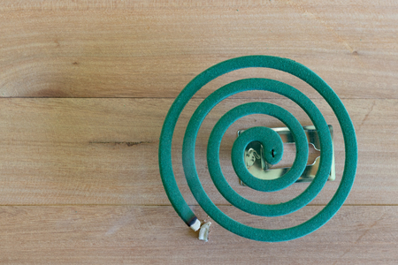 Green mosquito repellent burning and white smoke on wooden table with green blur light. Stock Photo