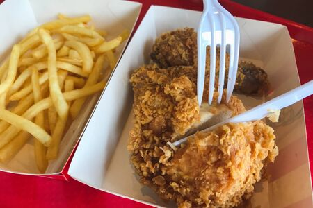 Eating fried chicken with french fries