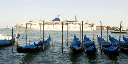 View of a cruise ship passing on the Venice lagoon and gondolas