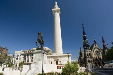 Photo of the George Washington Monument, Statue of La Fayette, and the United Methodist Church in Baltimore, Maryland. Mount Vernon cultural district. Stock Photo