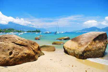 large rocks: beach landscape with large rocks, mountains, sailboats and sea Stock Photo