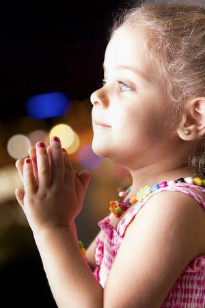 blonde yeux bleus: Cute petite fille en robe rose prier