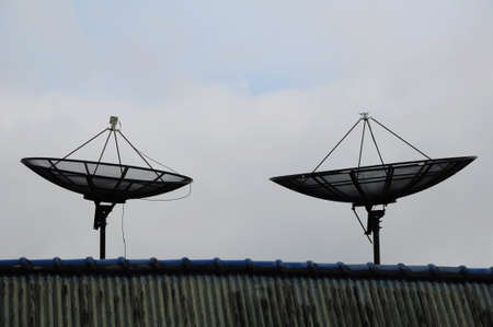 satellite dishes on roof with cloud photo