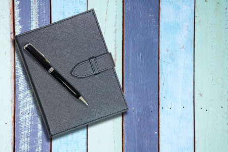 building planners: Black leather notebook with pen on vintage wooden