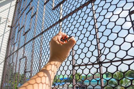 délivrance: Main de prisonnier en prison attraper maillage cage et que vous voulez la liberté Banque d'images