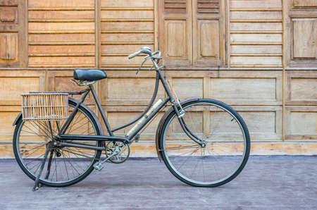 Vintage bcycle piedi vicino al muro di legno