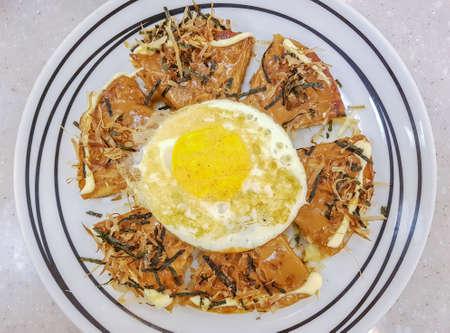 Cibo giapponese-Okonomiyaki con l'uovo fritto in cima Archivio Fotografico