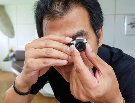 Fotografo uomo che tiene piccola macchina fotografica giocattolo Archivio Fotografico