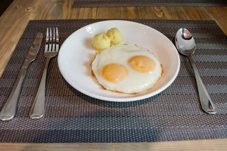 Twin fried eggs and mash potato on dish for breakfast.