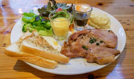 Pork steak served with toast, vegetable and mash potato