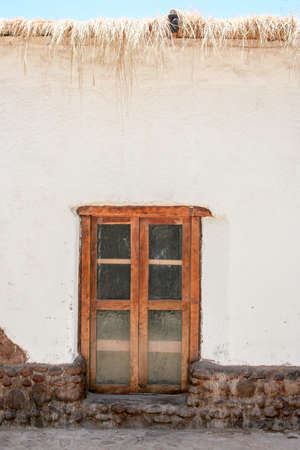 thatched: white house with brown window