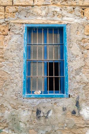gratings: and old blue wooden window behind metal gratings