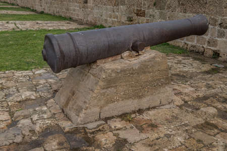 acer: an old metal canon mounted on a stone stand found in the city of Acer or Akko in Israel Stock Photo