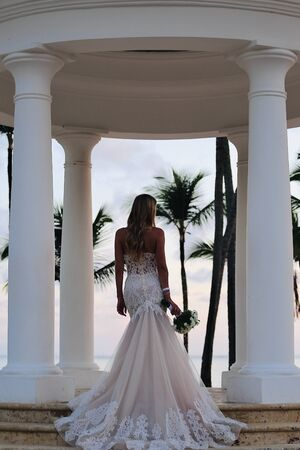 Bride in a wedding dress and long hair with bouquet white flowers on the ceremony in the ocean beach Stock Photo