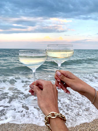 wineglasses with champagne in the hands on the beach and beautiful sea view
