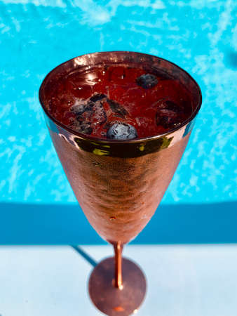 Wineglasses red color with champagne berries and ice in the pool background