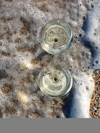 wineglasses with champagne on the beach and beautiful sea view