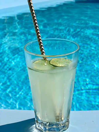 glass with cocktail and lemon in the pool background