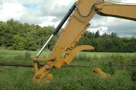 grader: excavator arm extended in grass