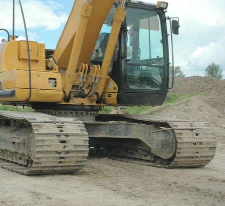 sand quarry: front tracksand cab  of yellow excavator Stock Photo