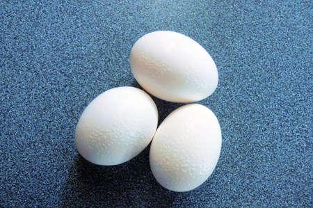 scrambled: three eggs sweating on a blue granite tabletop