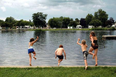 湖で泳いで午後を楽しむ 4 人の子供 写真素材