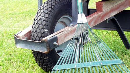 rake and wheelbarrow on grass