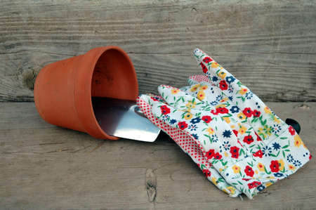 gardening gloves with clay pot laying  on side photo