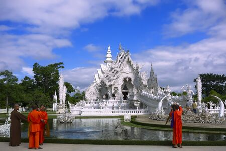 foreigners: Chiang Rai, Thailand - Jule 10, 2014: Monks in Wat Rong Khun. More well-known among foreigners as the White Temple, is a contemporary unconventional Buddhist temple in Chiang Rai, Thailand.