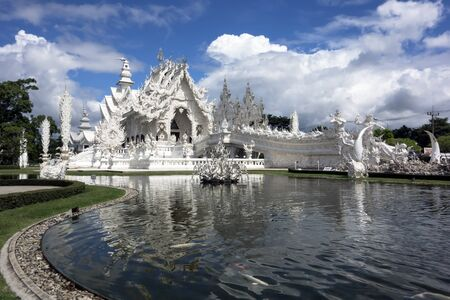 foreigners: Wat Rong Khun. More well-known among foreigners as the White Temple, is a contemporary unconventional Buddhist temple in Chiang Rai, Thailand. Stock Photo