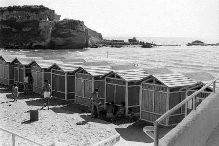 TORREGAVETA, NAPOLI, ITALY, 1960 - Young bathers chat in the shade of the bathhouse of Roman beach in Torregaveta, Naples, taken from the Roman ruins of Villa Vatia Redakční