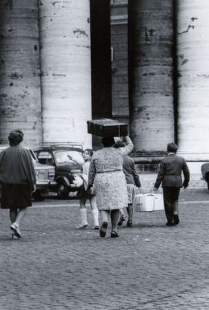ROME, ITALI, 1970 - Black and white picture of a family of emigrants near the colonnade of St. Peter's Square in Rome with their luggage