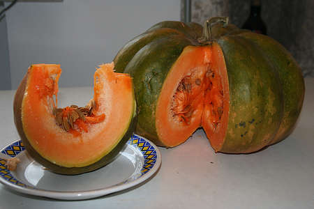A fresh green pumpkin with a nice slice on the plate is ready to satisfy your tastes