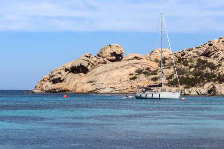 La Maddalena, Sardinia, Italy - Sailboat moors in Cala dello Spalmatore protected by the typical rocks of the bay