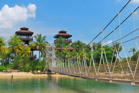 Wooden suspension bridge leading to paradise island, with hotels in the background photo
