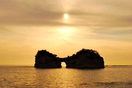 uniquely: Sun setting behind an uniquely shaped island with an opening at the bottom Stock Photo