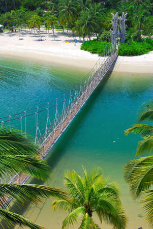 Wooden suspension bridge leading to paradise island surrounded by tropical trees and plants Stock Photo