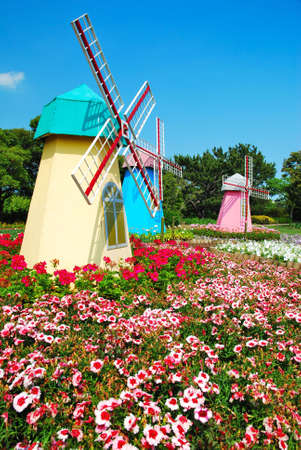 Model of three holland windmills in a park with field of flowers Stock Photo