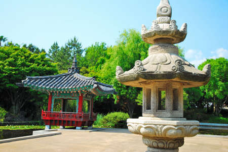 pavillion: Stone lamp with quaint, Asian-styled pavillion architecture in background