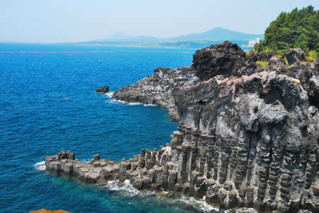 Unique rock formation with volcano in background