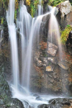 Close up shot of majestic waterfall splashing onto rocks Stock Photo