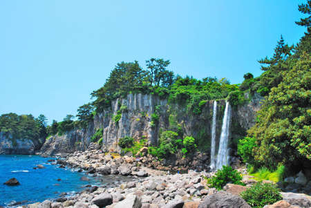 Far shot of majestic waterfall with sky background Stock Photo