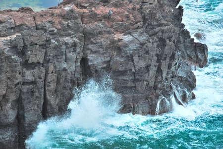 treacherous: Treacherous waves splashing on cliff rocks, displaying the power of nature